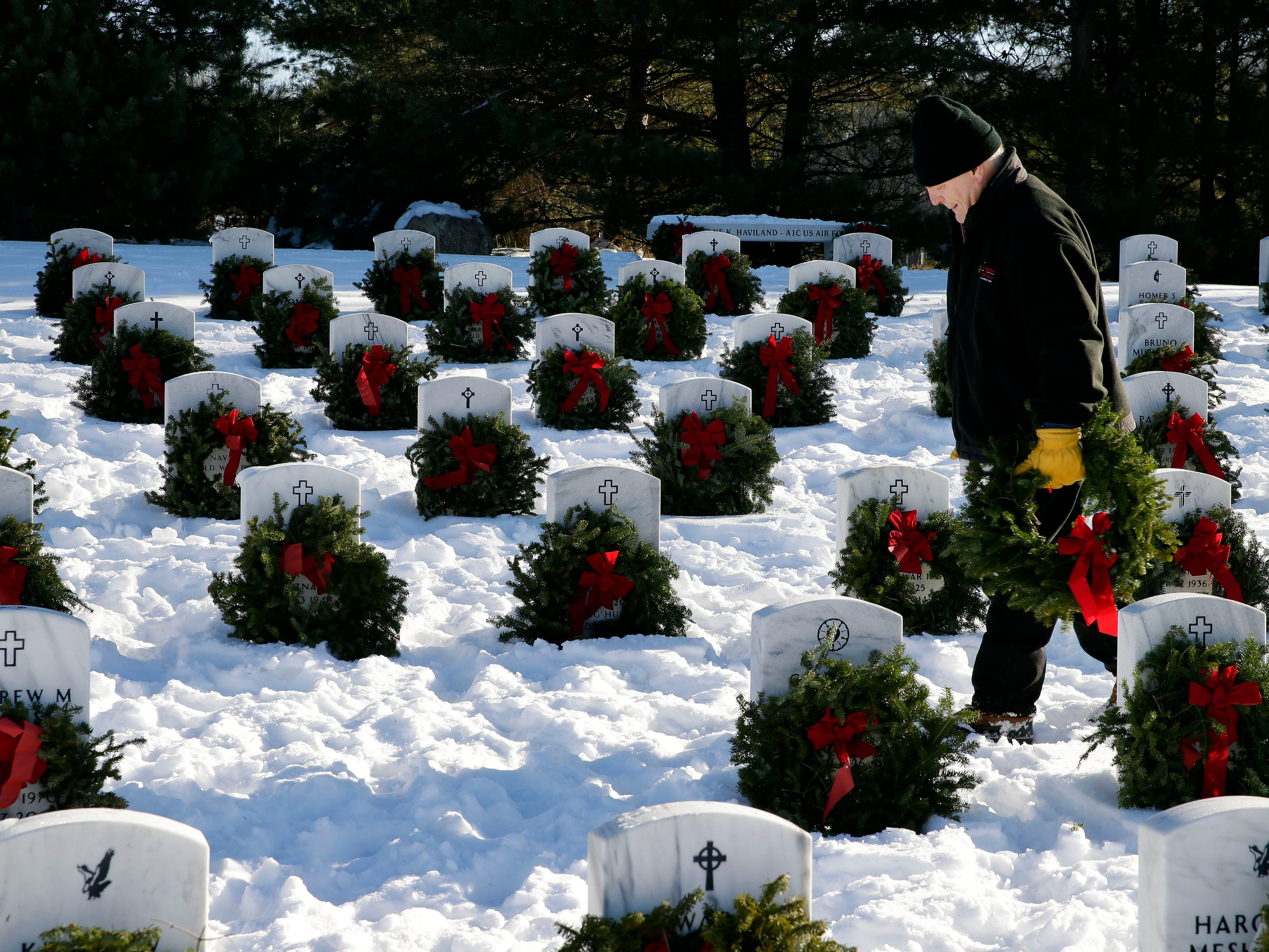 Steven Kalamen of Naperville, Illinois joins other volunteers taking part in Wreaths Across America Day at the Central Wisconsin Veterans Memorial Cemetery Saturday, December 15, 2018, in King, Wis. Over 7000 graves at King were honored with wreaths. Over 1400 other locations took part in the coordinated ceremony.