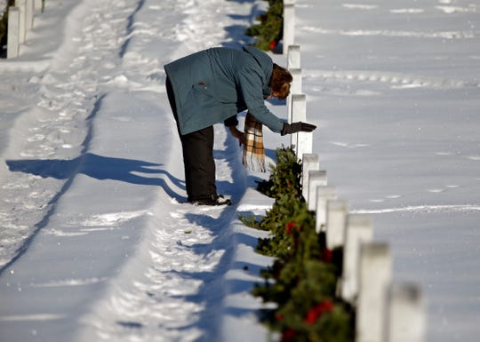 "Mary Young places a wreath and thanks the veteran for their service then pats the headstone and says ""God Bless You"" as she joins other volunteers taking part in Wreaths Across America Day at the Central Wisconsin Veterans Memorial Cemetery Saturday, Dec. 15, 2018, in King, Wis. More than 7,000 graves at King were honored with wreaths. Over 1,400 other locations took part in the coordinated ceremony."