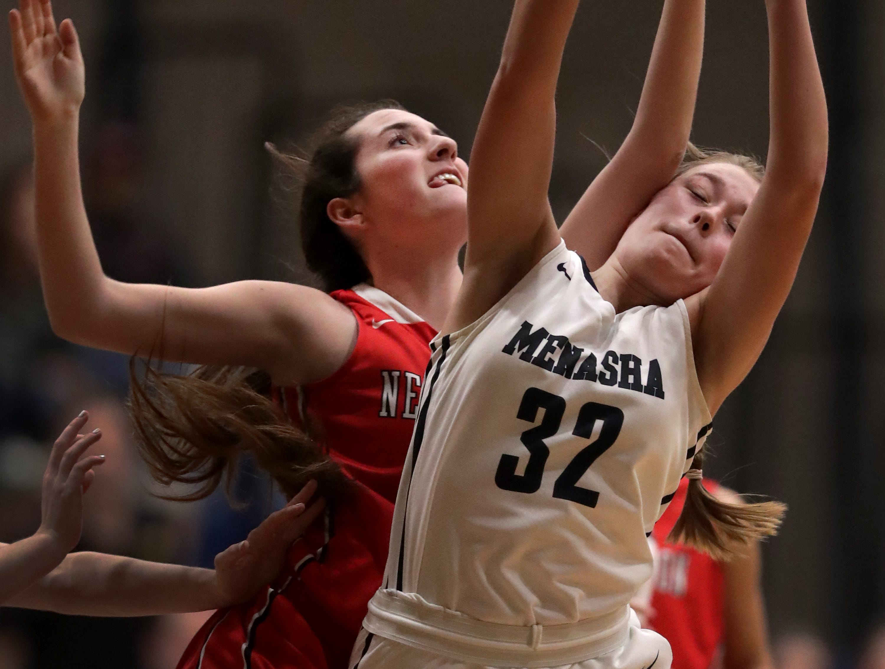 New London High School's #14 Meghan Besaw against Menasha High School's #32 Leah Johnson during their girls basketball game on Friday, December 14, 2018, in Menasha, Wis.