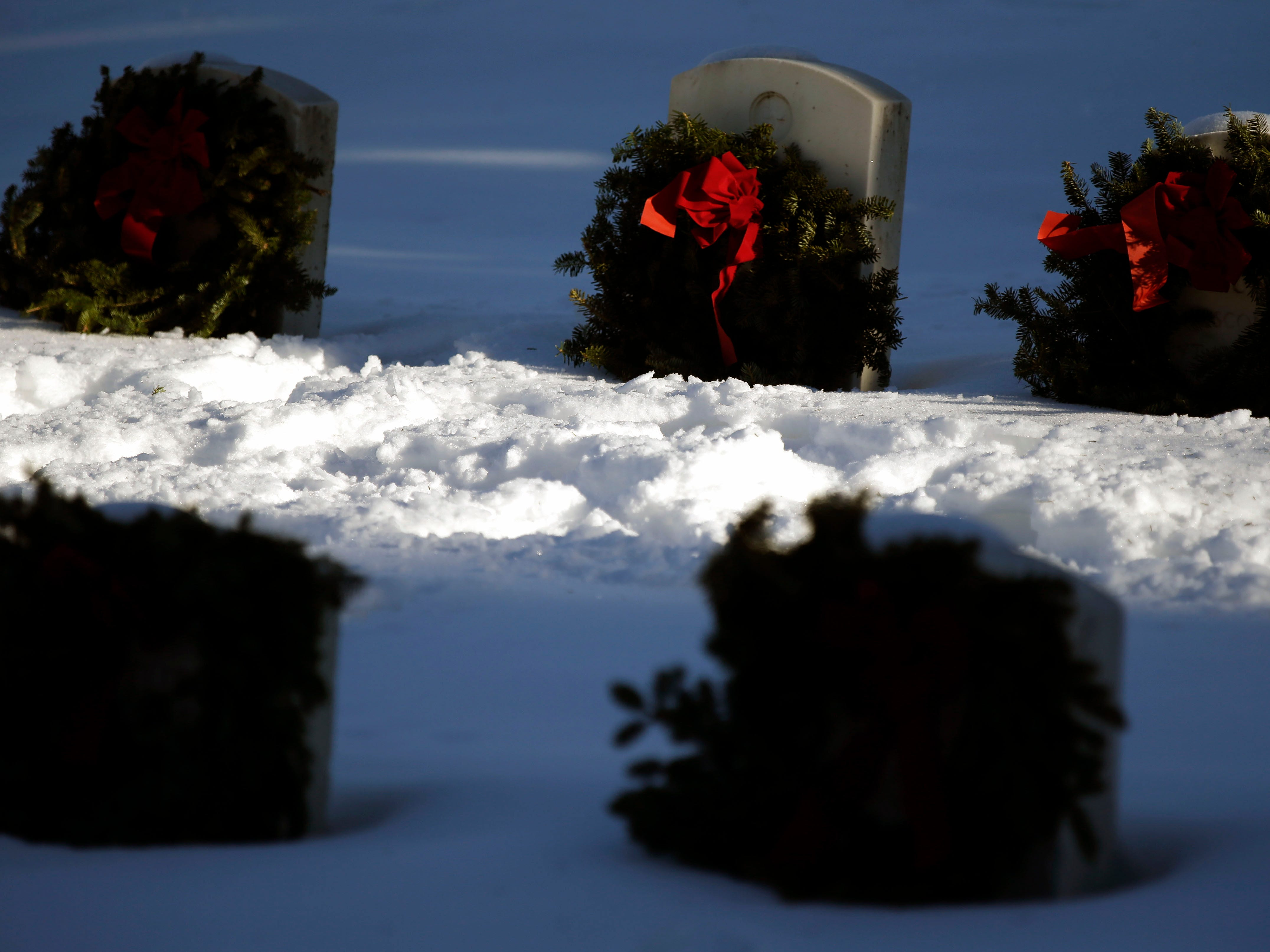 A shaft of sunlight illuminates wreaths after volunteers took part in Wreaths Across America Day at the Central Wisconsin Veterans Memorial Cemetery Saturday, December 15, 2018, in King, Wis. Over 7000 graves at King were honored with wreaths. Over 1400 other locations took part in the coordinated ceremony.