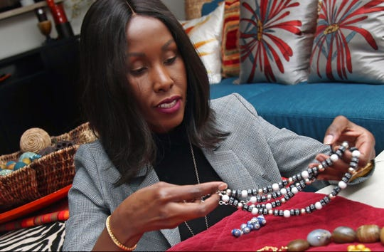 Shamila Nduriri, who owns Dalasini, an upscale jewelry company, holds some of her jewelry in her Minneapolis apartment. Nduriri, who studied finance in college, saved aggressively when she worked for a corporation and continues to put money aside now that she owns Dalasini.