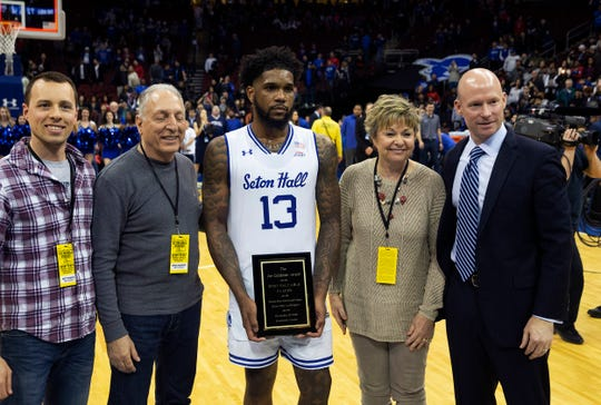Seton Hall's Myles Powell holds his Joe Calabrese Most Valuable Player trophy after game. Surrounding him are members of the late sportswriters's family and Hall coach Kevin Willard.