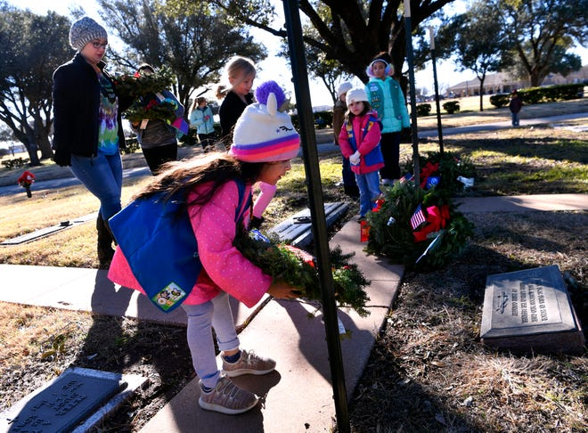 Evalett Salinas, 6, sets wreath honoring deceased U.S. Air Force veterans in the veterans section of Elmwood Memorial Park on Saturday. Members of Girl Scout Troop 7001 placed wreaths for each service branch at the cemetery. Wreaths Across America is a program that provided holiday wreaths at veterans' graves. Volunteers placed wreaths at Elmwood Memorial Park and at Texas State Veterans Cemetery at Abilene. Wreaths also were collected at Elmwood to be distributed in Big Country cemeteries.