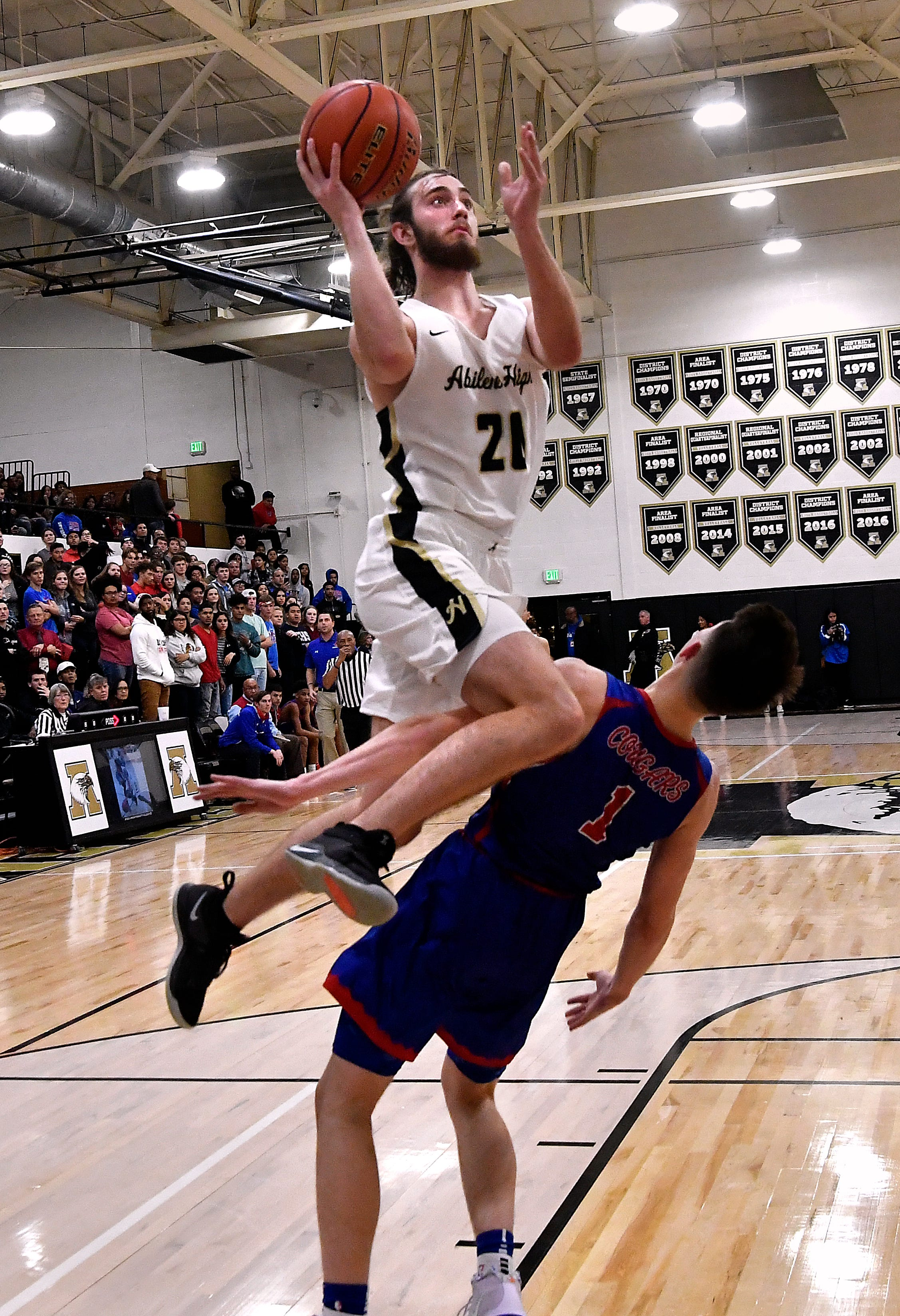 Abilene High forward Brian Patton climbs up the shoulder of Cooper High forward Deven Bailey during Friday's crosstown basketball game Dec. 14, 2018. Final score was 63-52, Abilene High.
