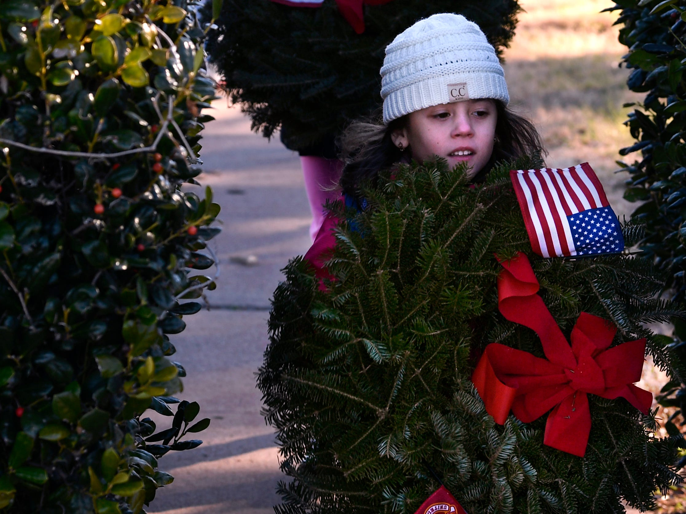 Adalynn Ferguson, 5, carries a wreath for deceased U.S. Marine veterans as Emerson Mills, 6, follows her with the Coast Guard wreath Saturday Dec. 15, 2018. The girls are members of Girl Scout Troop 7001 who placed wreaths for each branch of the service in the veterans section of Elmwood Memorial Park. Wreaths Across America is a program that provided holiday wreaths at veterans' graves. Volunteers placed wreaths at Elmwood Memorial Park and at Texas State Veterans Cemetery at Abilene. Wreaths were also collected at Elmwood to be distributed in Big Country cemeteries.