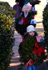 Adalynn Ferguson, 5, carries a wreath for deceased U.S. Marine veterans as Emerson Mills, 6, follows her with the Coast Guard wreath Saturday The girls are members of Girl Scout Troop 7001 who placed wreaths for each branch of the service in the veterans section of Elmwood Memorial Park.