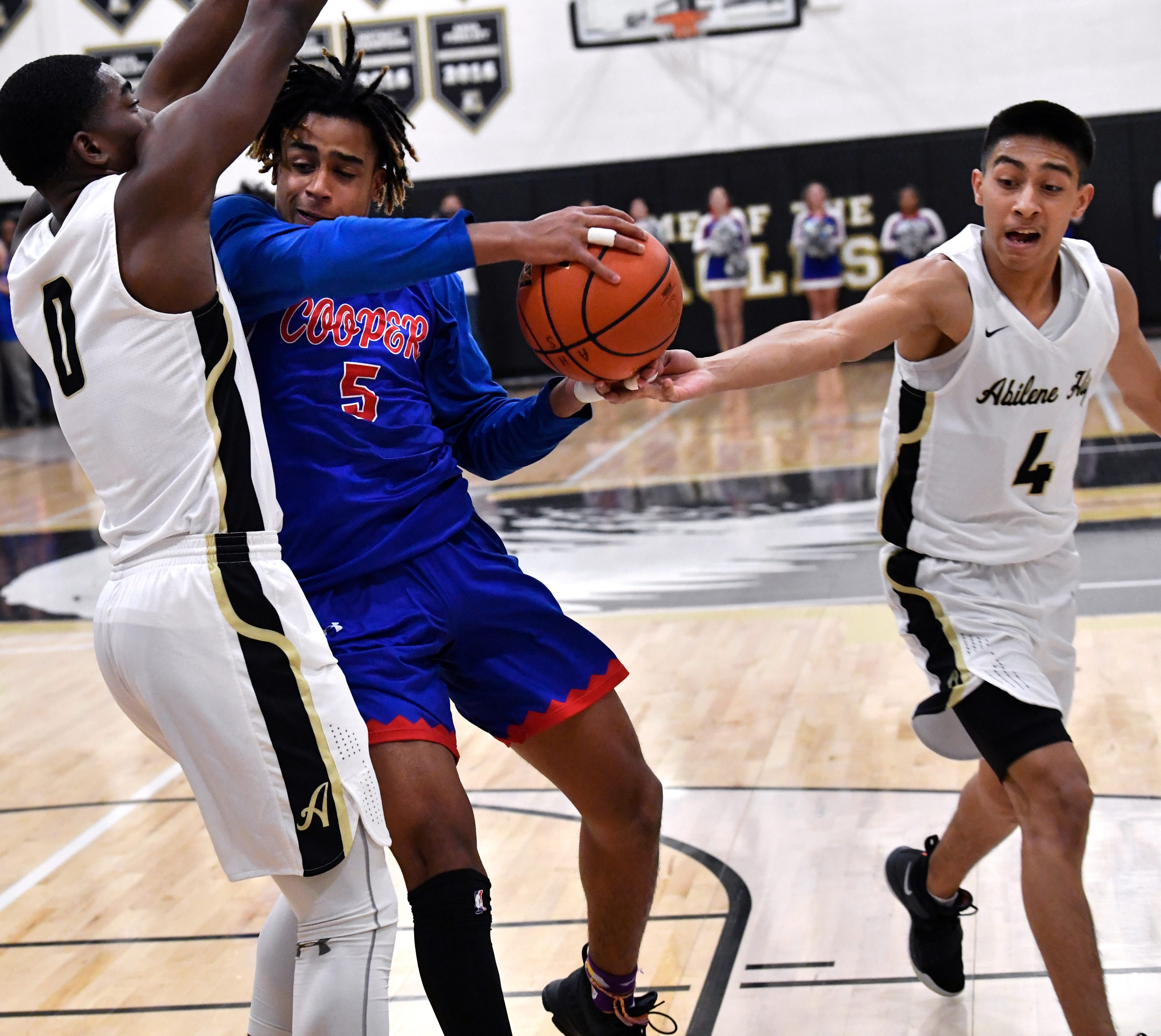 Cooper High forward Aeneas Favors shoulders into Abilene High forward Donte Cuffy as his teammate Jojo Escobedo tries to tip the ball away from Favors Friday Dec. 14, 2018. Final score was 63-52, Abilene High.