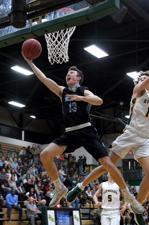 Enka's Jake Smith goes up for a shot against Reynolds during their game at Reynolds High School on Dec. 14, 2018. The Rockets defeated the Jets 77-55.