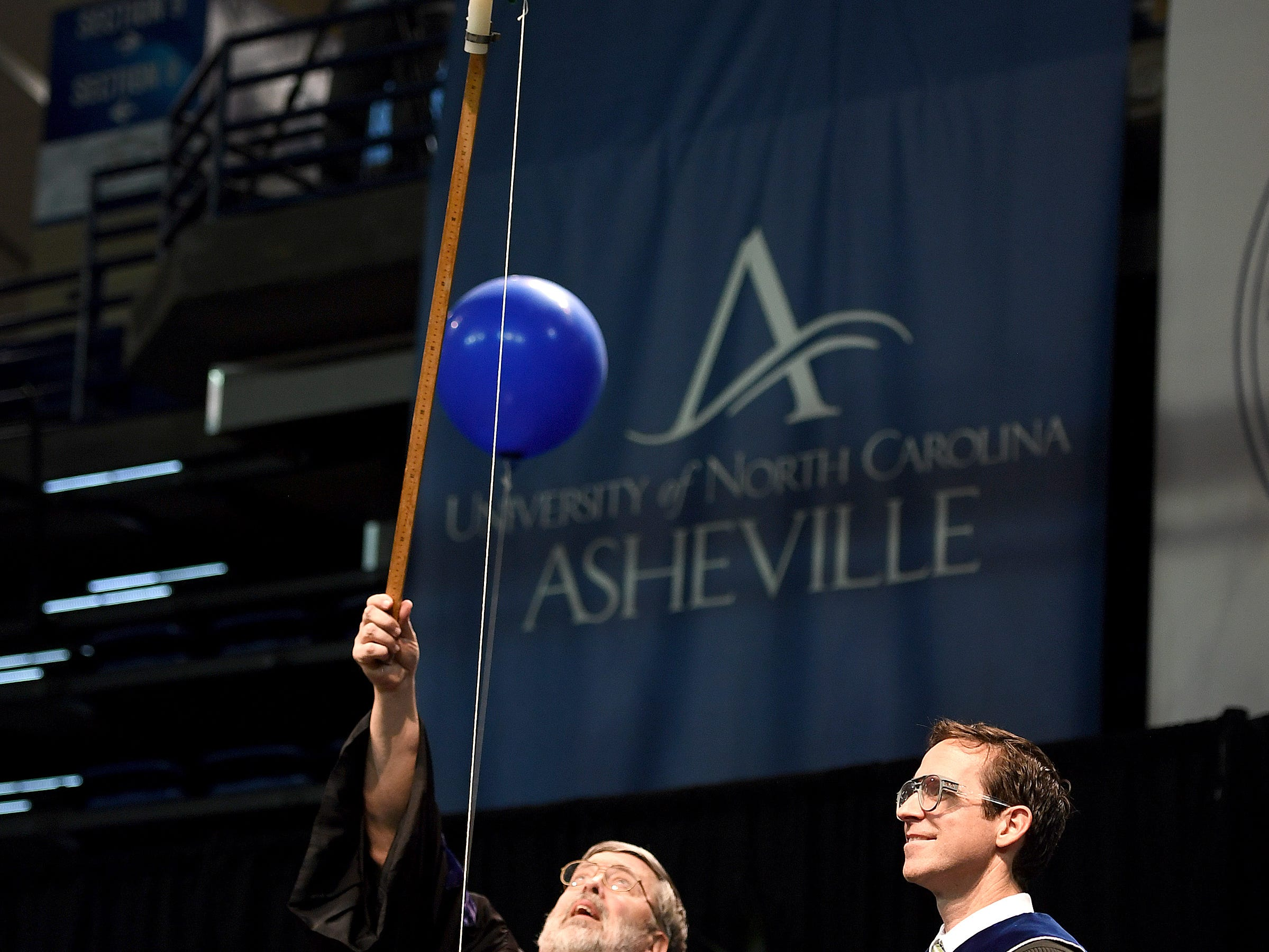 """UNC Asheville chemistry professor and keynote speaker Bert Holmes pops a balloon with a candle imparting the lesson """"don't be a dud"""" during the winter commencement ceremony at Kimmel Arena on Dec. 14, 2018. He popped three balloons, each producing a different chemical reaction and leaving a different lesson for the graduates."""