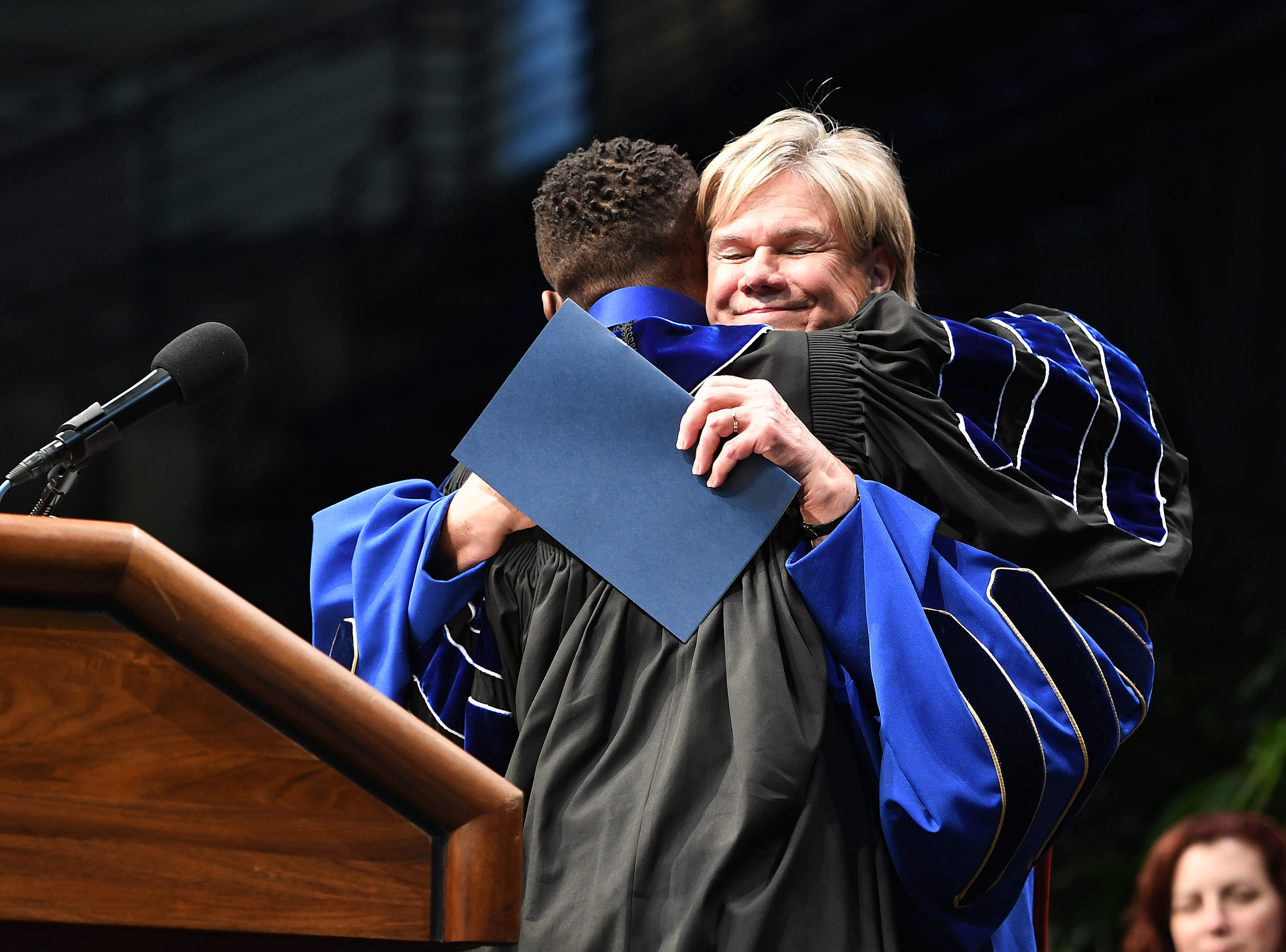 UNC Asheville chancellor Nancy J. Cable hugs student speaker and Student Government Association president Michael Davis as he approaches the podium during the winter commencement ceremony at Kimmel Arena on Dec. 14, 2018.