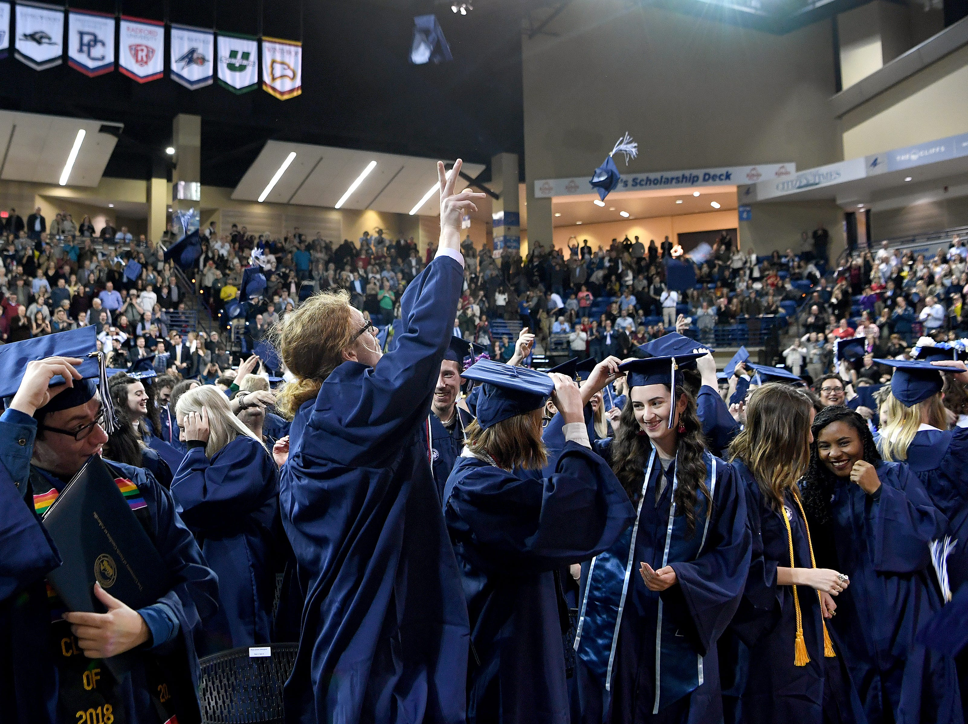 UNC Asheville graduates throw their caps at the end the winter commencement ceremony at Kimmel Arena on Dec. 14, 2018.