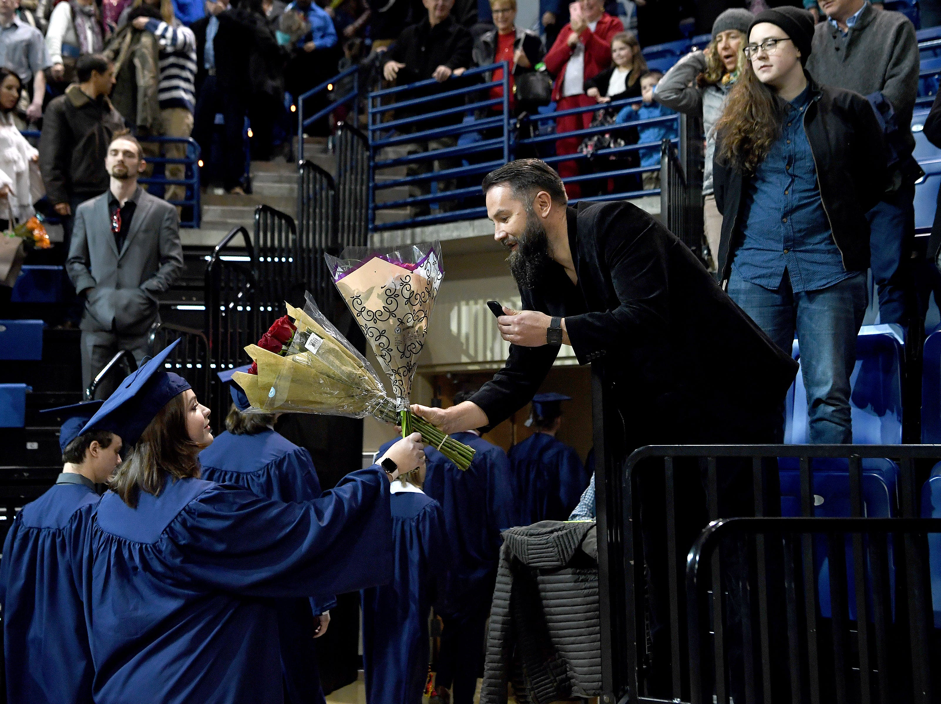 Vladimir Grebenyuk holds flowers for this daughter, Ekaterina, as he exits the stadium after the UNC Asheville winter commencement ceremony at Kimmel Arena on Dec. 14, 2018.