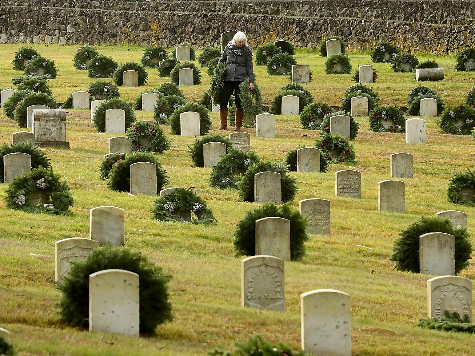 Mary Morin stops to read a headstone as she places wreaths during the Wreaths Across America event at the Washington Veterans Home Cemetery in Port Orchard on Saturday, December 15, 2018.