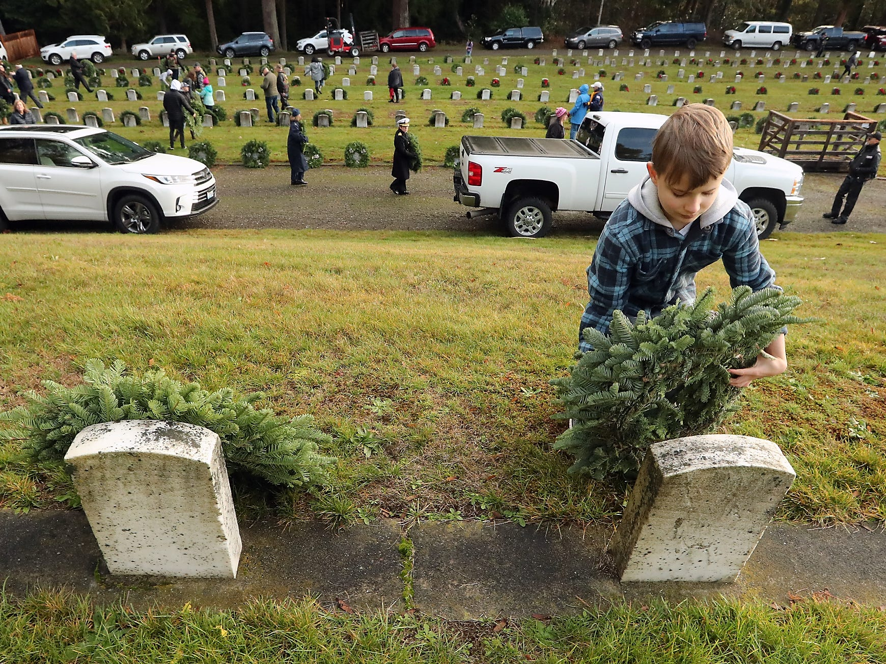 Elijah Rossiter, 9, places a wreath against a headstone during the Wreaths Across America event at the Washington Veterans Home Cemetery in Port Orchard on Saturday, December 15, 2018.