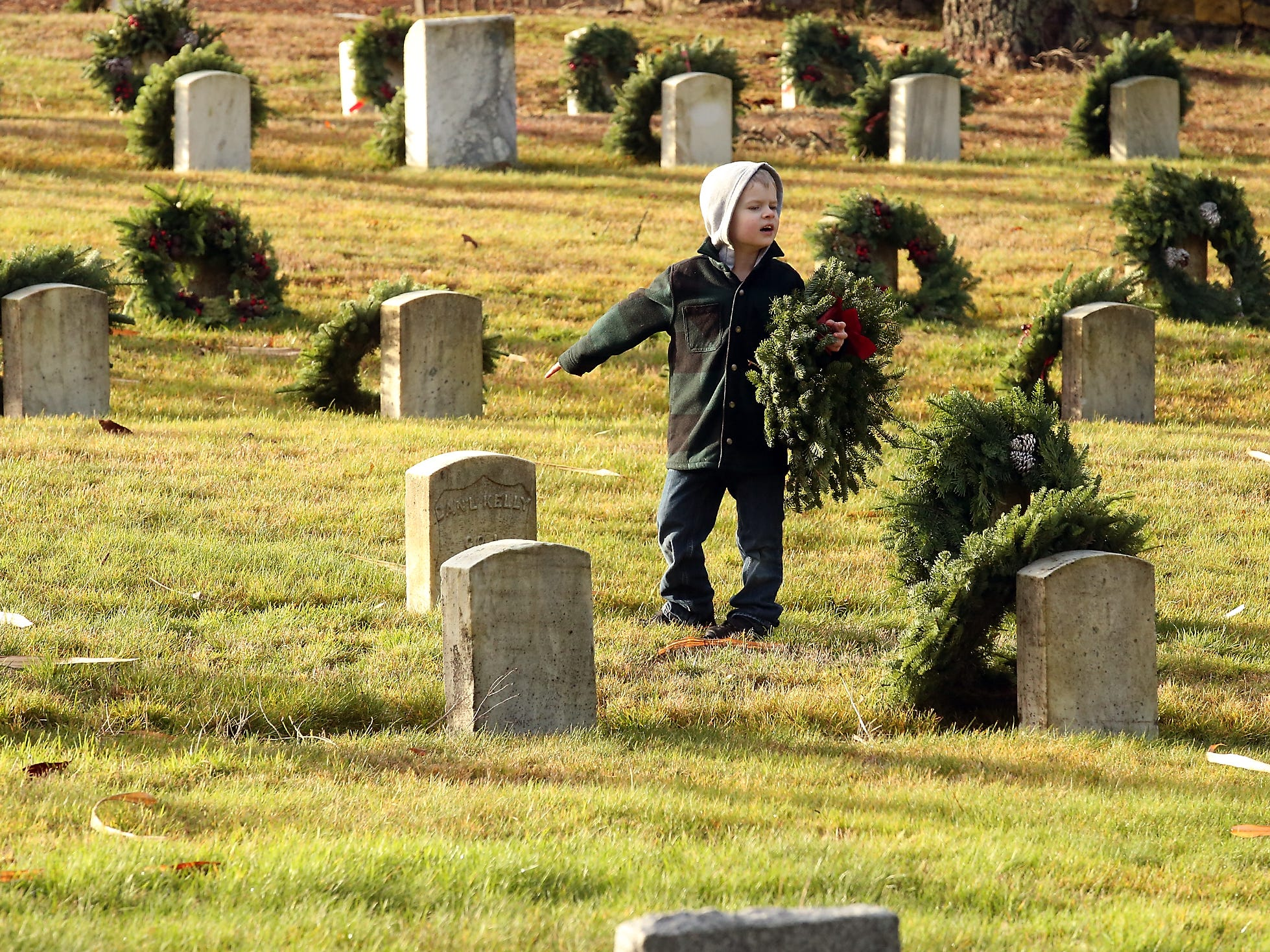 Ethan Rossiter, 6, points to an open headstone as he looks for a place to put his wreath during the Wreaths Across America event at the Washington Veterans Home Cemetery in Port Orchard on Saturday, December 15, 2018.