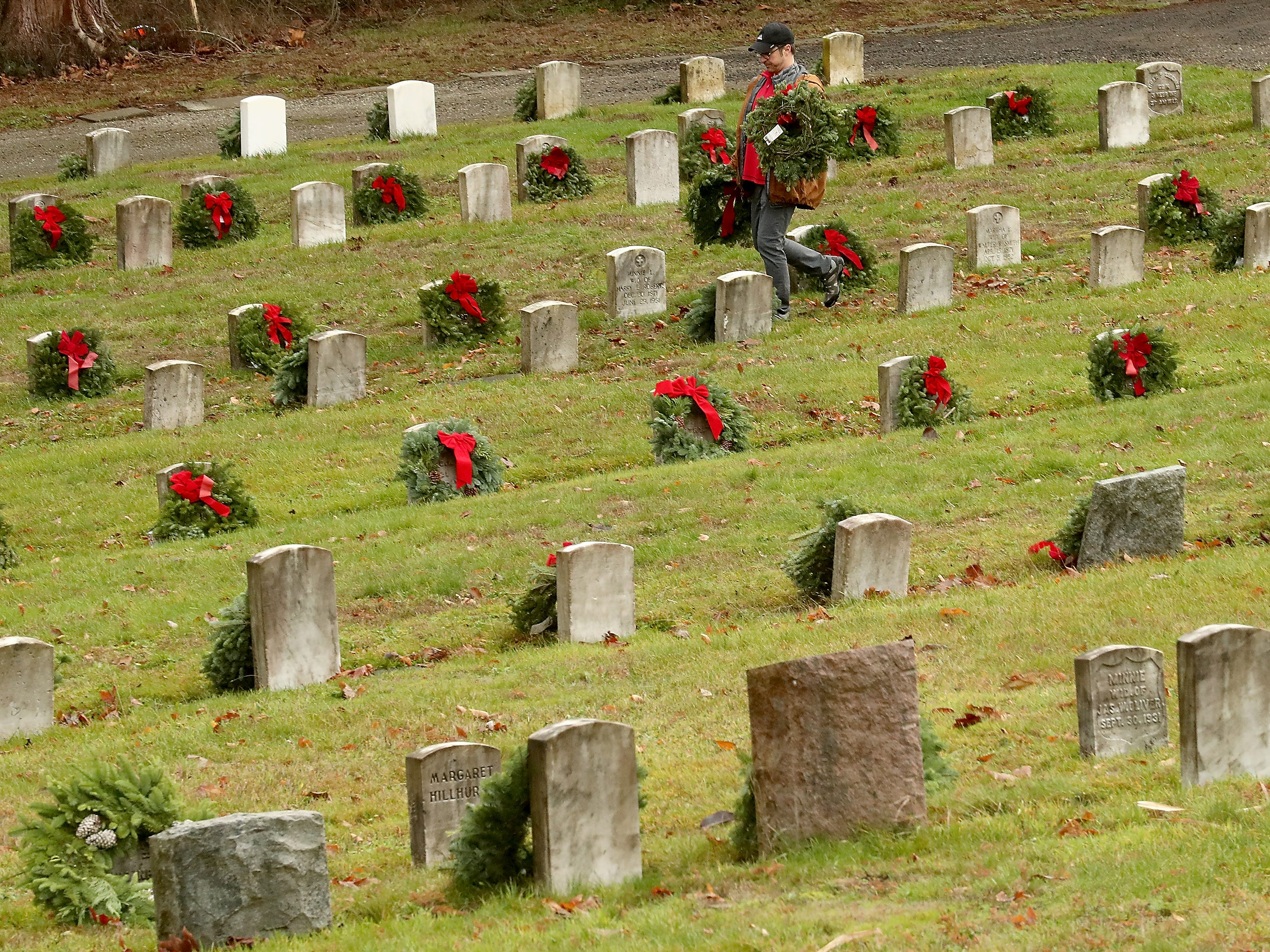 Volunteer Jeff Rose walks among the headstones as he and fellow volunteers place 2143 wreaths during the Wreaths Across America event at the Washington Veterans Home Cemetery in Port Orchard on Saturday, December 15, 2018. The event was organized locally by Veterans Allegiance VMC and VFW Post 2669.