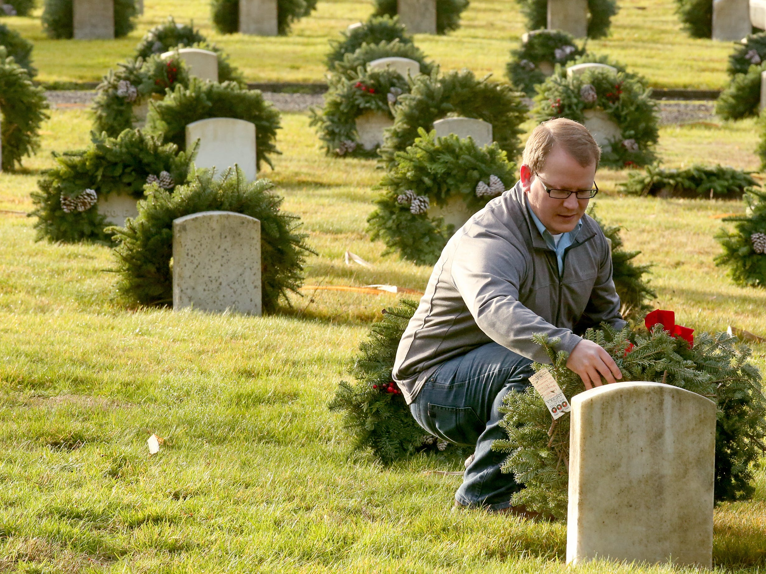 Brenden Rossiter places a wreath against a headstone during the Wreaths Across America event at the Washington Veterans Home Cemetery in Port Orchard on Saturday, December 15, 2018.