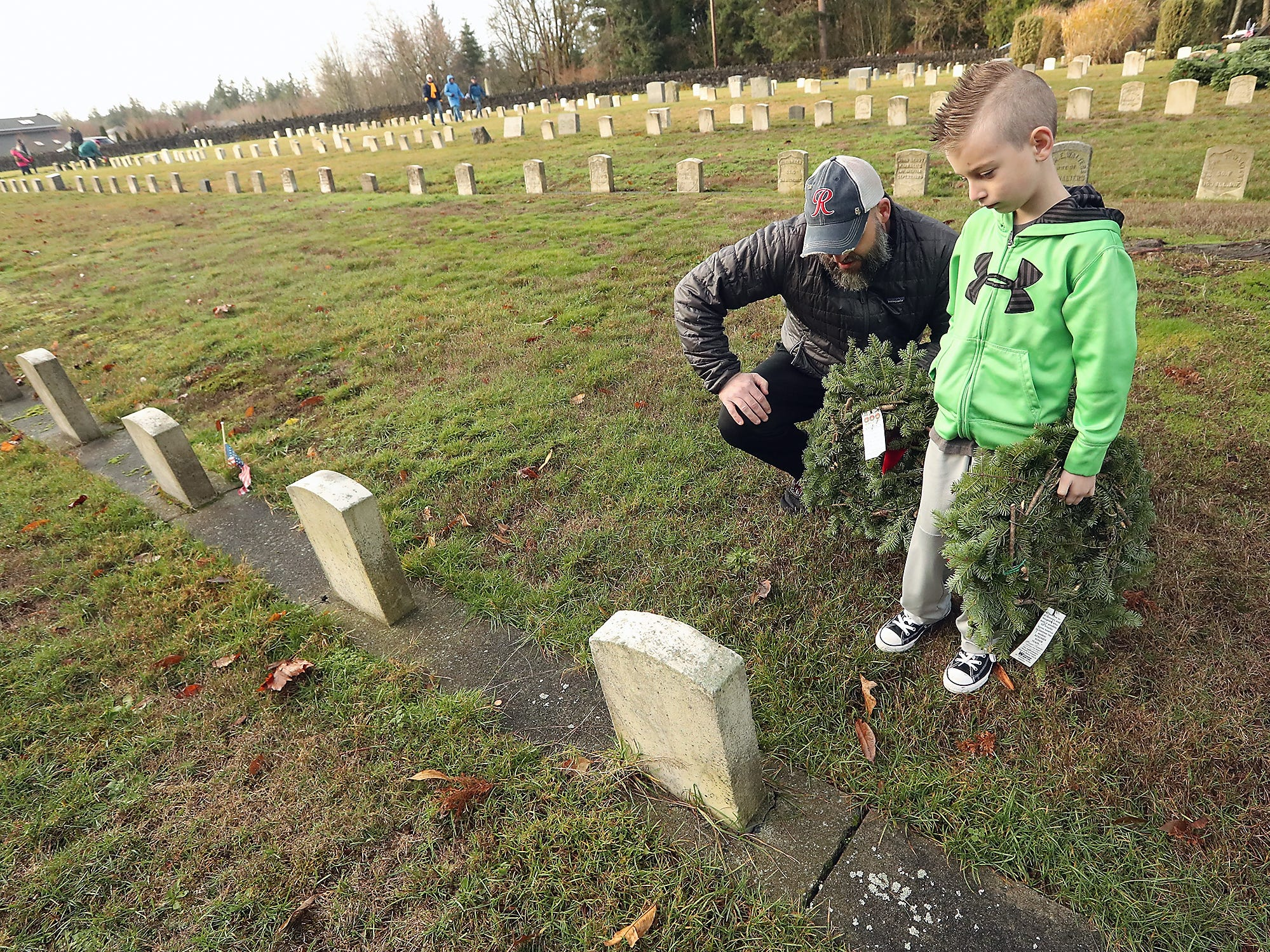 Mark Haase and son Griffin, 8, read the name on the headstone before placing a wreath against it during the Wreaths Across America event at the Washington Veterans Home Cemetery in Port Orchard on Saturday, December 15, 2018.