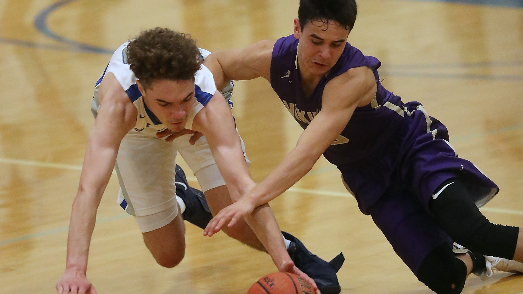 Olympic's Caleb Morgan (left) and North Kitsap's Johny Olmsted dive for a loose ball during their game at Olympic High on Friday, December 14, 2018.
