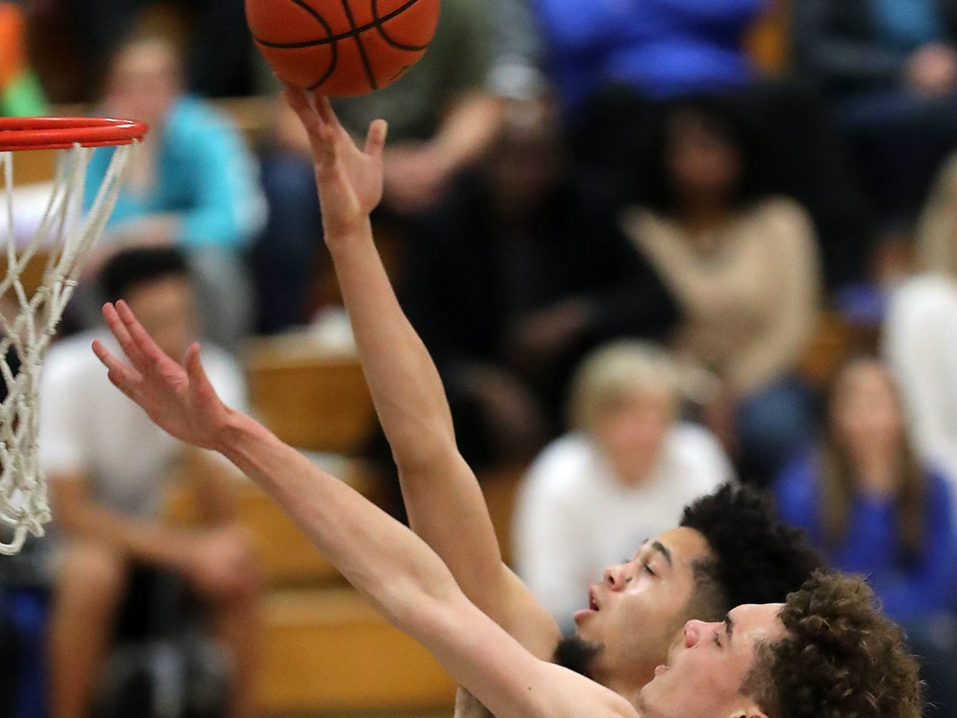 Olympic's Caleb Morgan (right) tries to block the shot of North Kitsap's Shaa Humphrey during the first half of their game at Olympic High on Friday, December 14, 2018.