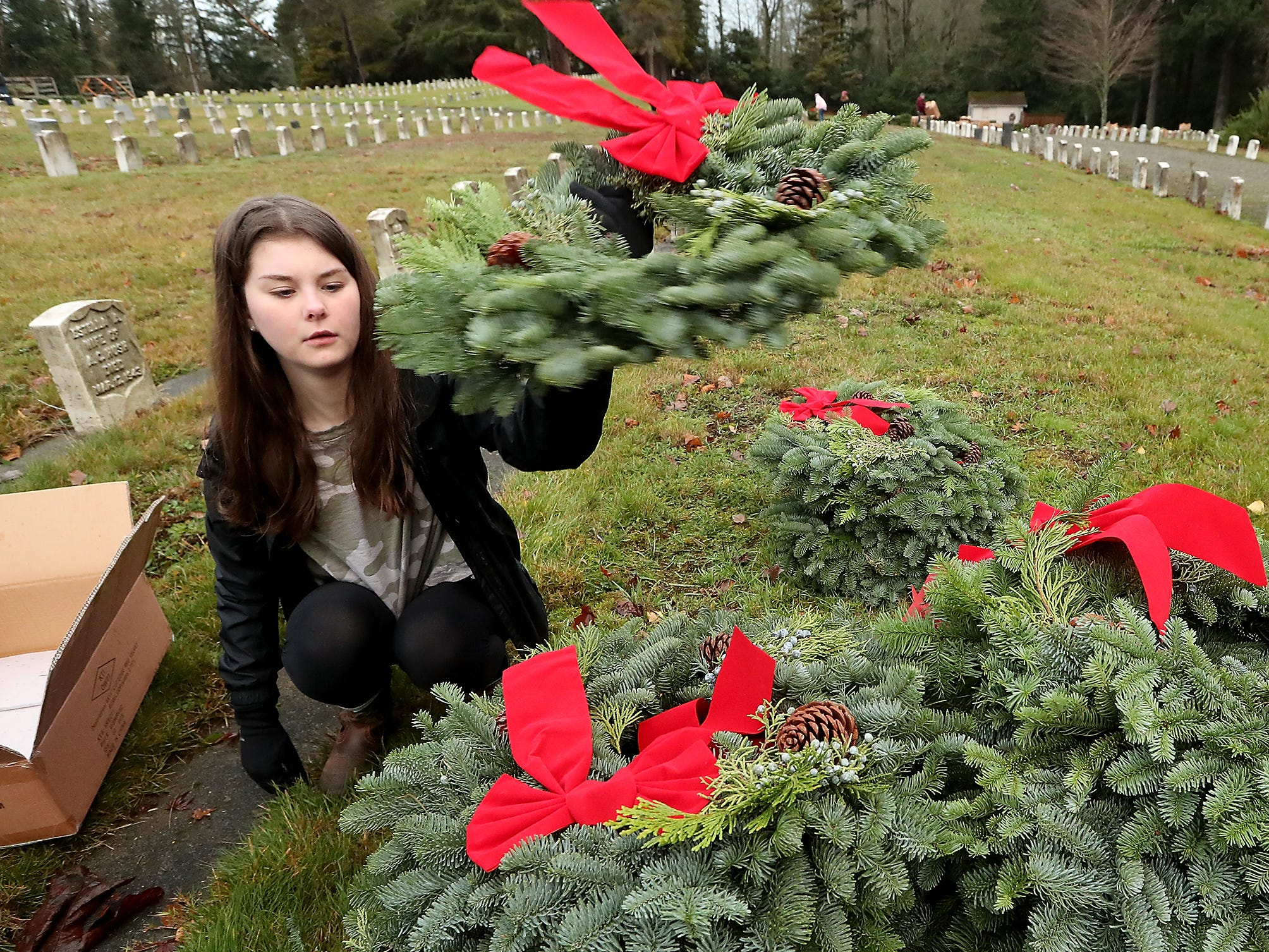 Volunteer Sydney Alexander places a wreath on the pile after affixing a bow to it as she and fellow volunteers get the wreaths ready for placement at the Washington Veterans Home Cemetery in Port Orchard on Saturday, December 15, 2018.