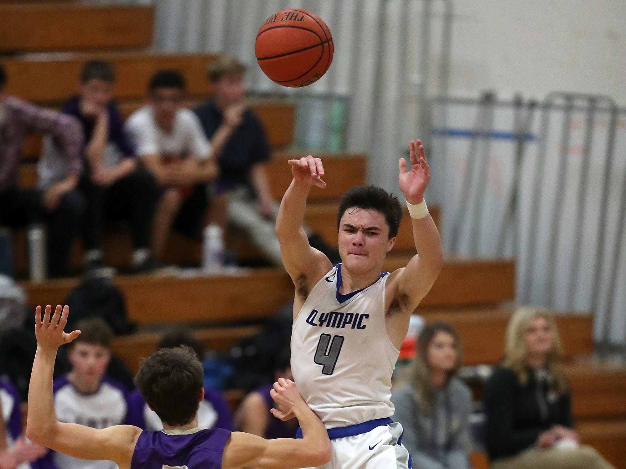 Olympic's Brandon Barron (4) makes a pass over North Kitsap's Grant Baker (3) to Greg Brehmer during the second half of their game at Olympic High on Friday, December 14, 2018.