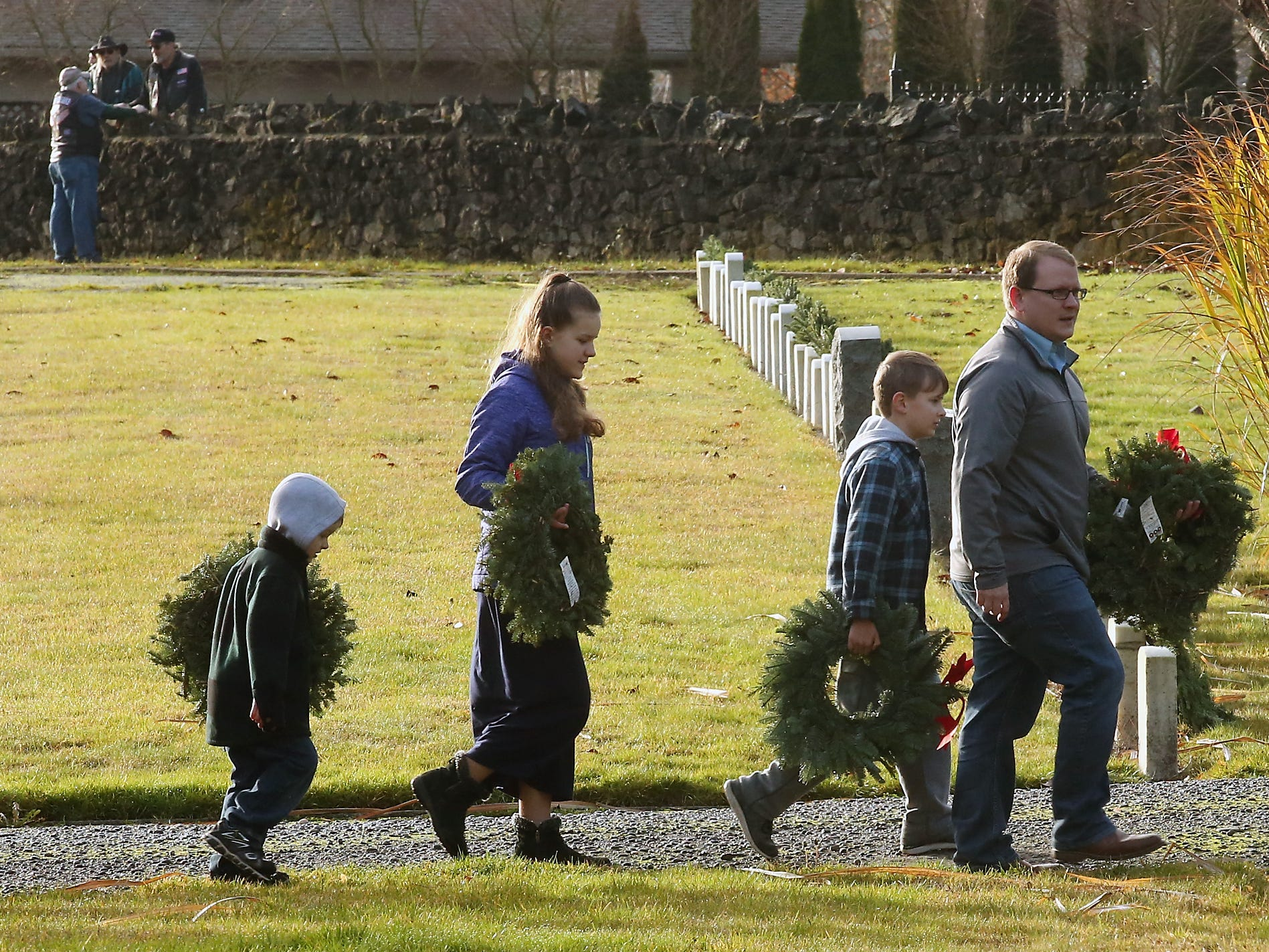 The Rossiter family (back to front) Ethan, Evelynn, Elijah, and father Brenden take part in the Wreaths Across America event at the Washington Veterans Home Cemetery in Port Orchard on Saturday, December 15, 2018.