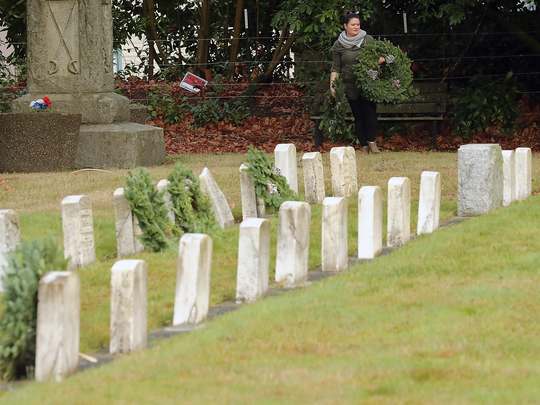Jessica Rossiter looks for open headstones of veterans to place the final few wreaths on during the Washington Veterans Home Cemetery in Port Orchard on Saturday, December 15, 2018.