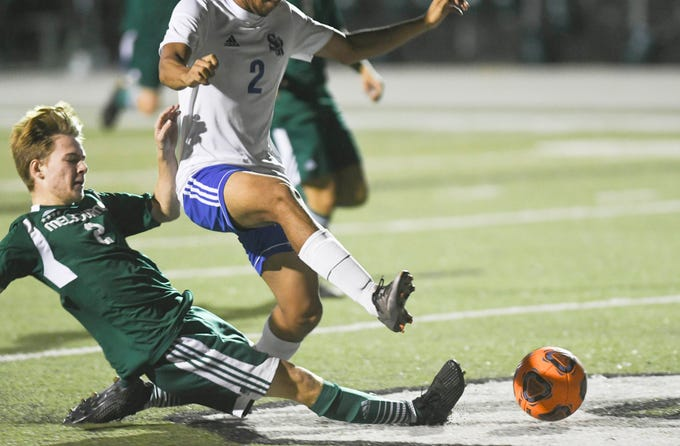 Melbourne's Max Marcos tackles the ball away from Gilberto Garcia of Sebastian River during Friday's game in Melbourne.