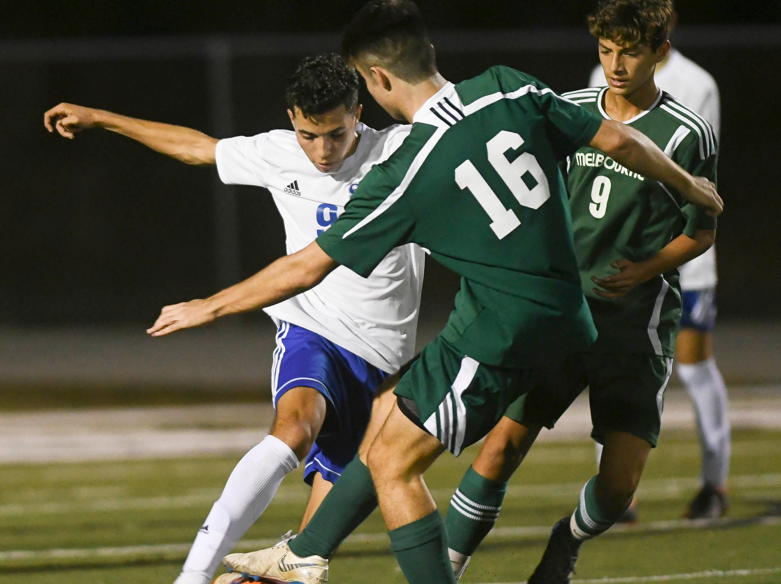 Miguel Perez of Sebastian River tries to push through the defense of Calvin MacDonald (16) and Osas Osaro of Melbourne during Friday's game in Melbourne.