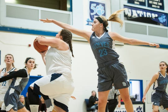South Burlington's Maddy Collins (23) leaps to block the shot by MMU's Hannah Angolano (23) during the girls basketball game between the South Burlington Wolves and the Mount Mansfield Cougars at MMU High School on Friday night December 14, 2018 in Jericho.