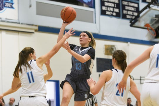 South Burlington's Ava MacDonough (13) leaps to take a shot over MMU's Elana Philbrick (11) during the girls basketball game between the South Burlington Wolves and the Mount Mansfield Cougars at MMU High School on Friday night December 14, 2018 in Jericho.