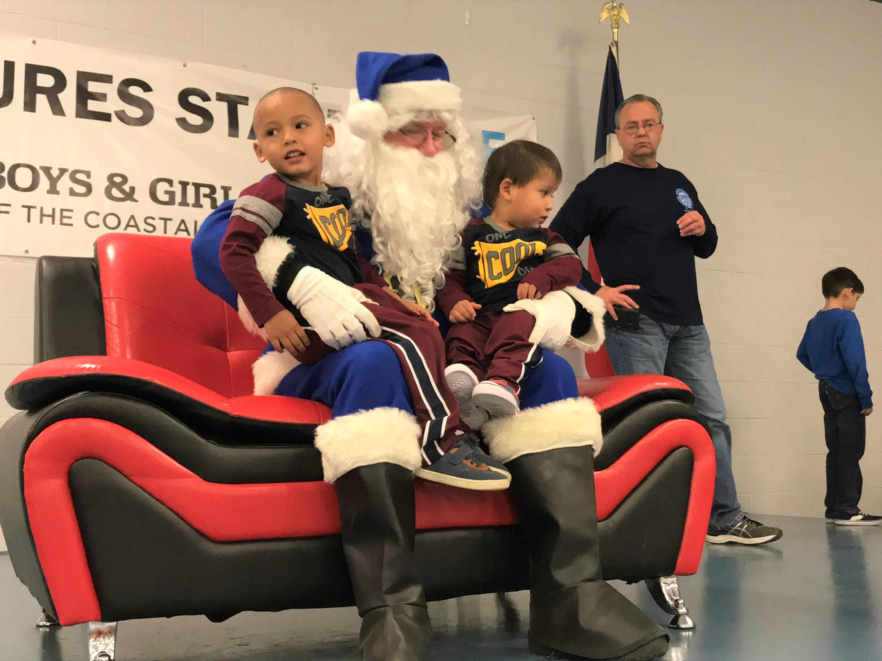 Children sit on Blue Santa's lap at the Boys and Girls Club of the Coastal Bend on Saturday, Dec. 15, 2018. Santa brought dozens of toys for the children at the club.