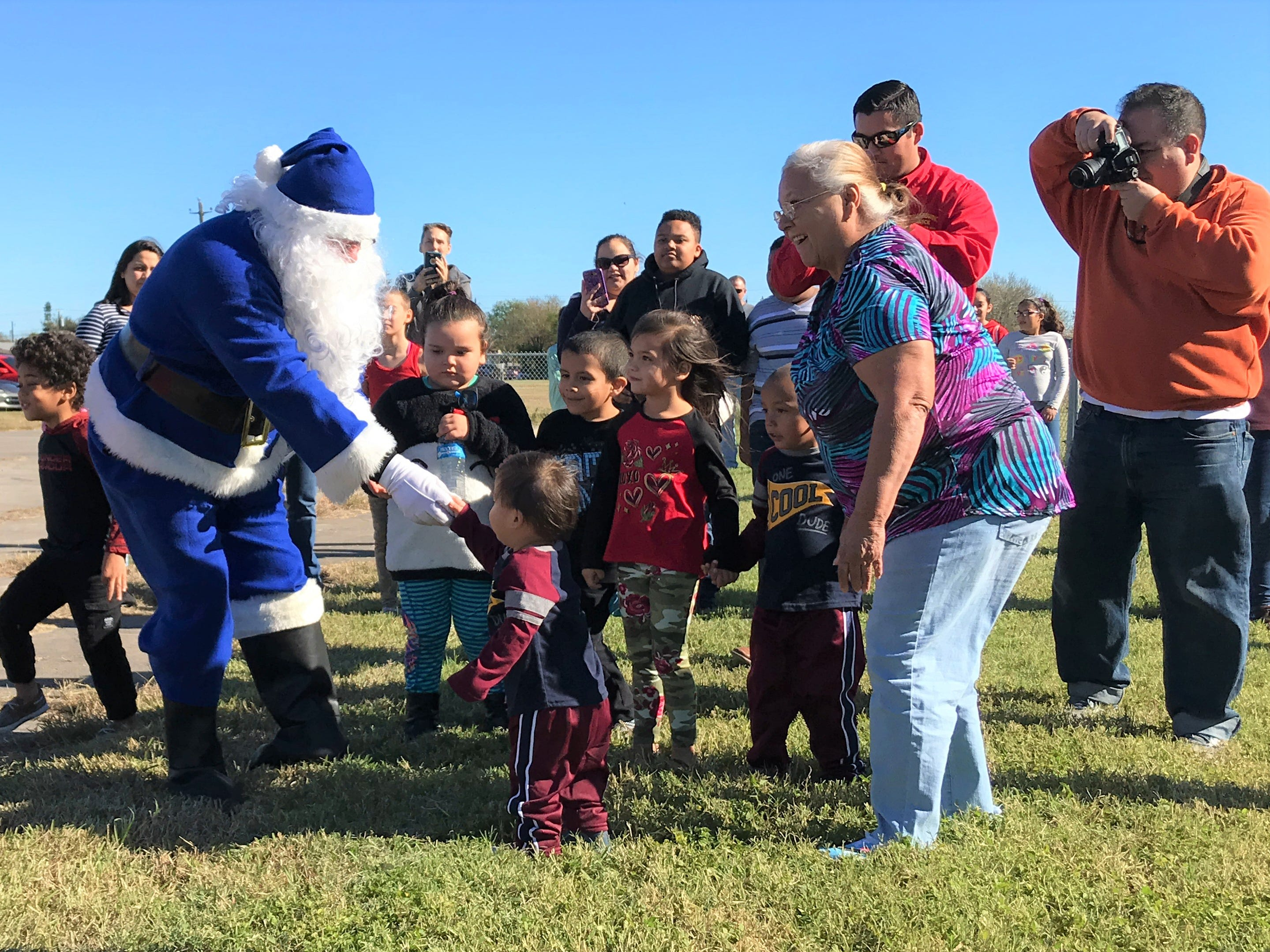 Blue Santa shakes the hands of children at the Boys and Girls Club of the Coastal Bend on Saturday, Dec. 15, 2018.