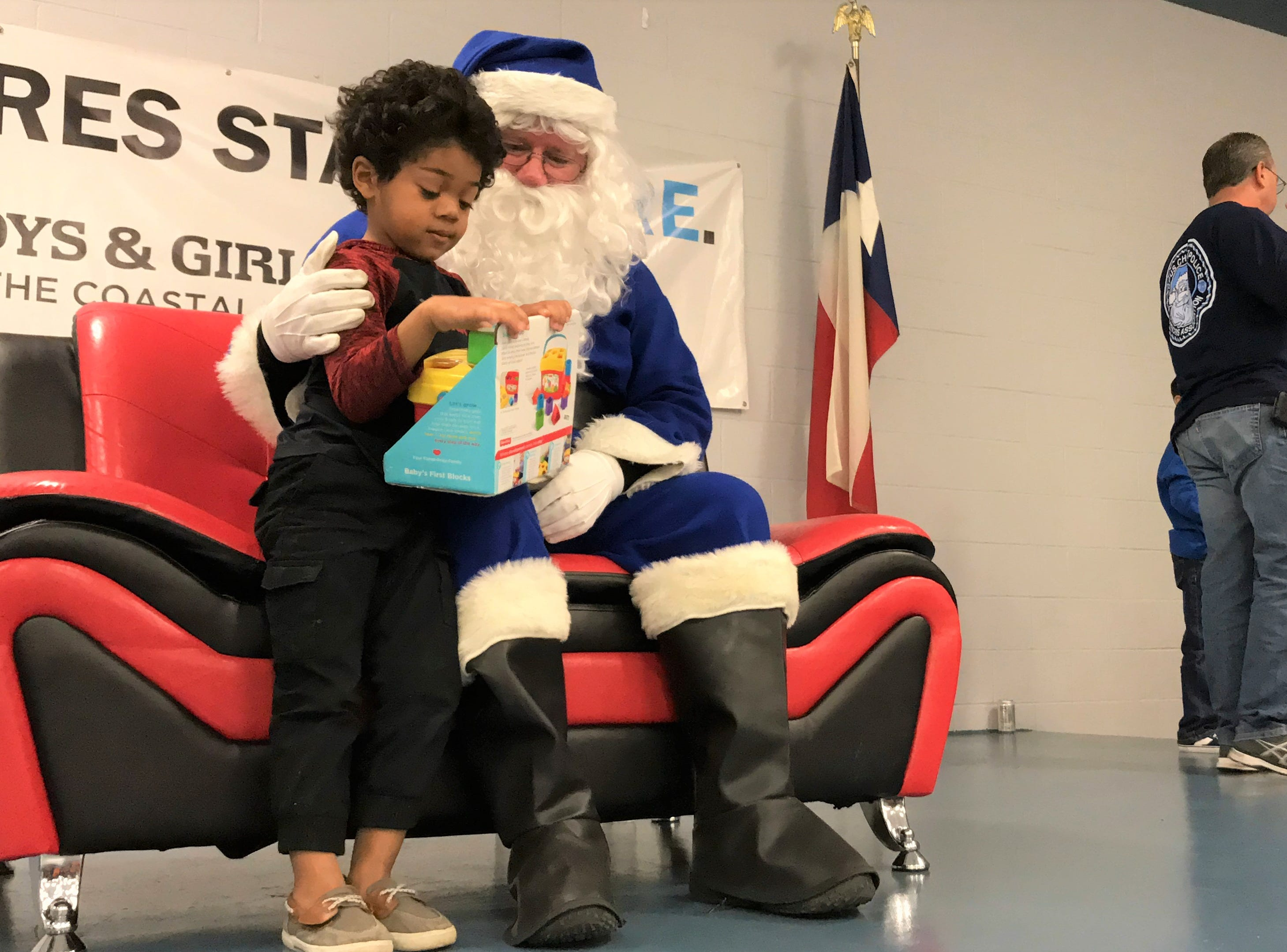 Blue Santa gives toys to children at the Boys and Girls Club of the Coastal Bend on Saturday, Dec. 15, 2018.