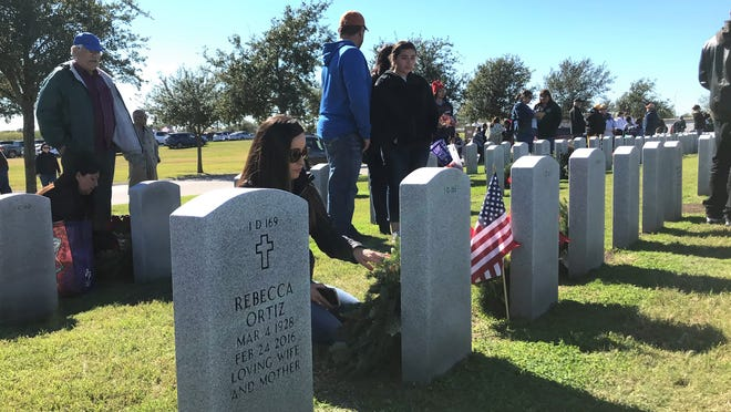 Families and volunteers place wreaths on graves during Wreaths Across America at the Coastal Bend State Veterans Cemetery on Saturday, Dec. 15, 2018.