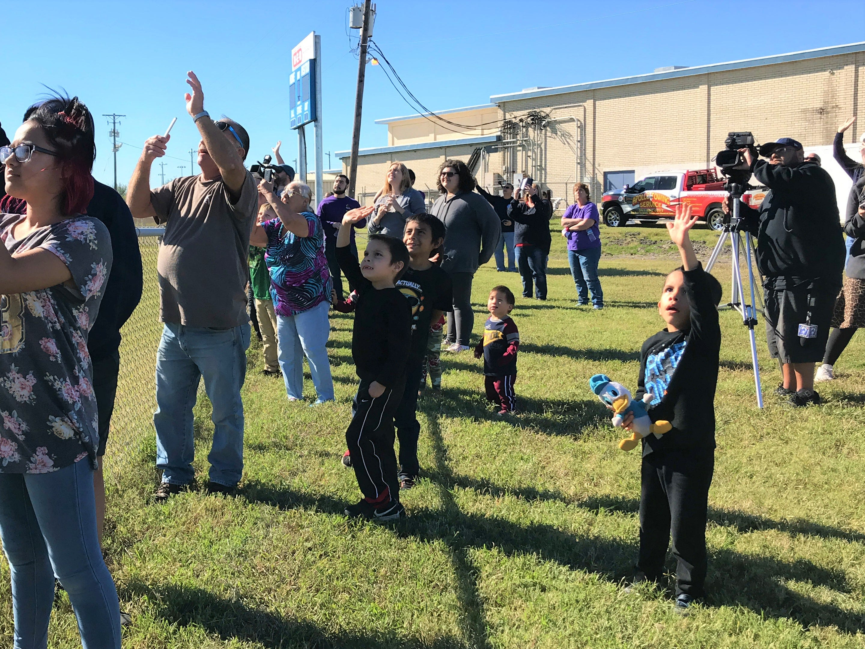 Parents and children wave at Blue Santa in a U.S. Coast Guard helicopter as he lands at the Boys and Girls Club of the Coastal Bend on Saturday, Dec. 15, 2018.