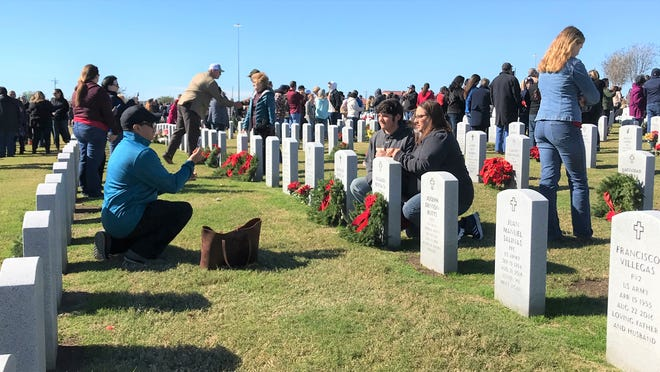 Families place wreaths on headstones and take photos during Wreaths Across America at the Coastal Bend State Veterans Cemetery on Saturday, Dec. 15, 2018.