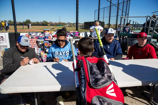 Michael Franco (from left), a player for Tampa Bay Rays minor league, Michael Berglung, a player for Tampa Bay Rays organization, Michael Cantu, San Diego Padres minor leaguer, and Aaron Hernandez, a Los Angles Angeles farmhand, sign autographs following a baseball camp and annual Trevino Toy Drive at John Paul II High School on Saturday, December 15, 2018.