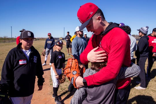 Aaron Hernandez, a Los Angeles Angels minor league player, gets a hug following a baseball camp and annual Trevino Toy Drive at John Paul II High School on Saturday, December 15, 2018.