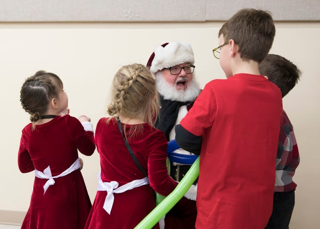 Santa Claus greets several children as he arrives at the Ross County Fairgrounds to hand out presents to foster children from various counties in Ohio.