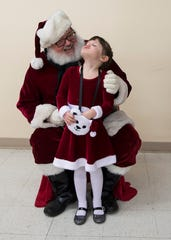 Lucy Mendenhall has an enjoyable time with Santa Claus at the annual foster Christmas party in Chillicothe, Ohio. Mendenhall was adopted by Dan and Robin Mendenhall almost a year ago. The couple has adopted seven children and fostered five.