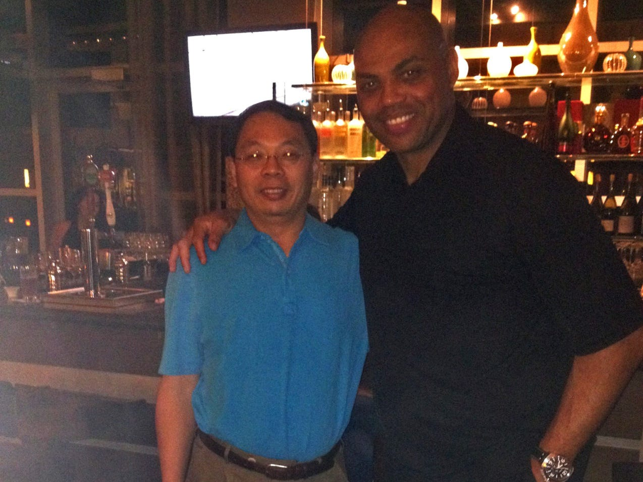 Lin Wang, left, takes a picture with basketball legend Charles Barkley.