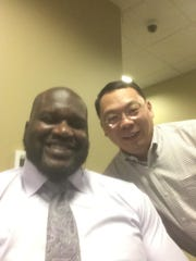 Lin Wang, right, takes a picture with basketball legend Shaquille O'Neal.