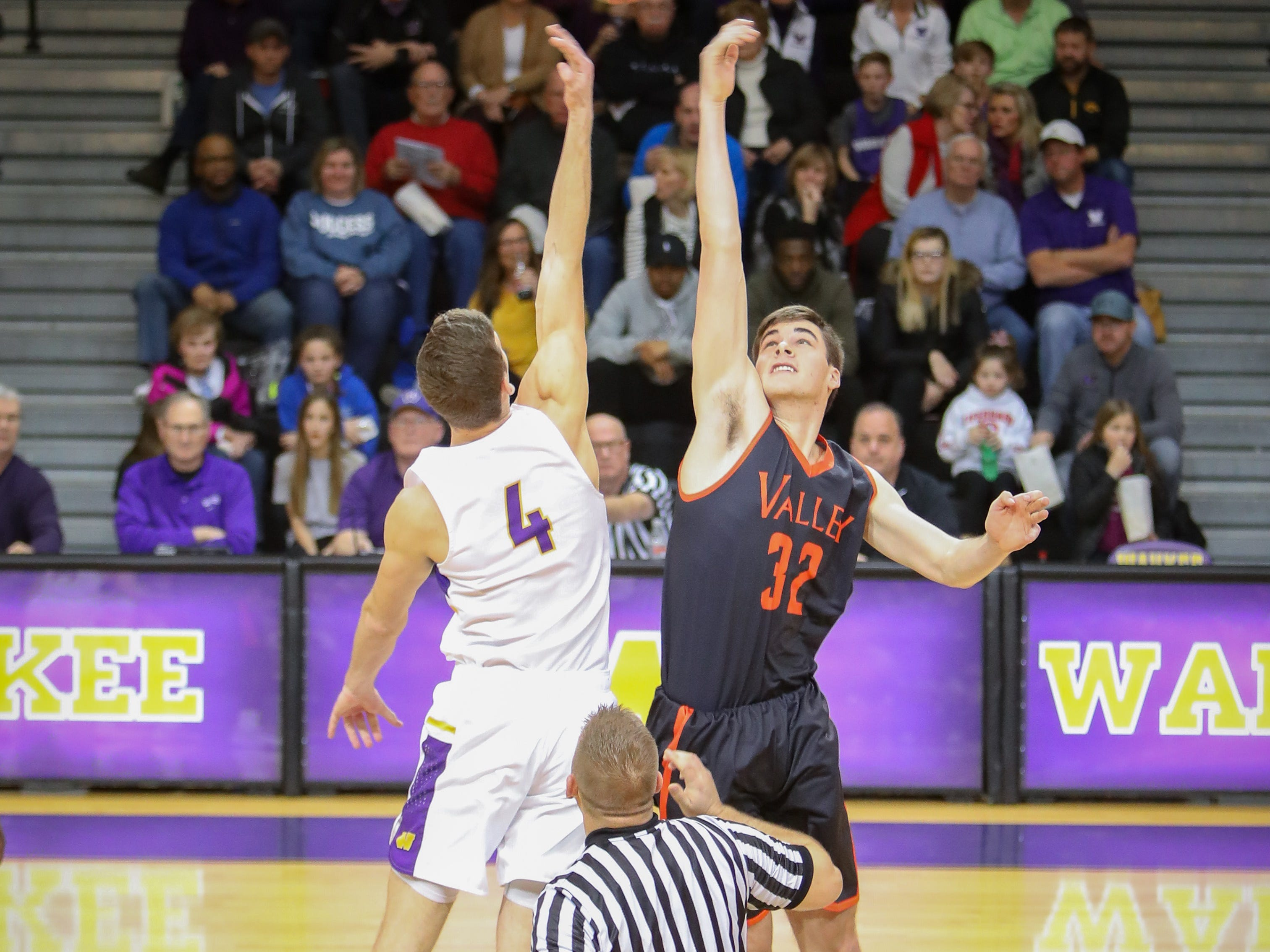 Waukee senior Dylan Jones and Valley junior Will Berg go for the tip-off during a boys high school basketball game between the Valley Tigers and the Waukee Warriors at Waukee High School on Dec. 14, 2018 in Waukee, Iowa.