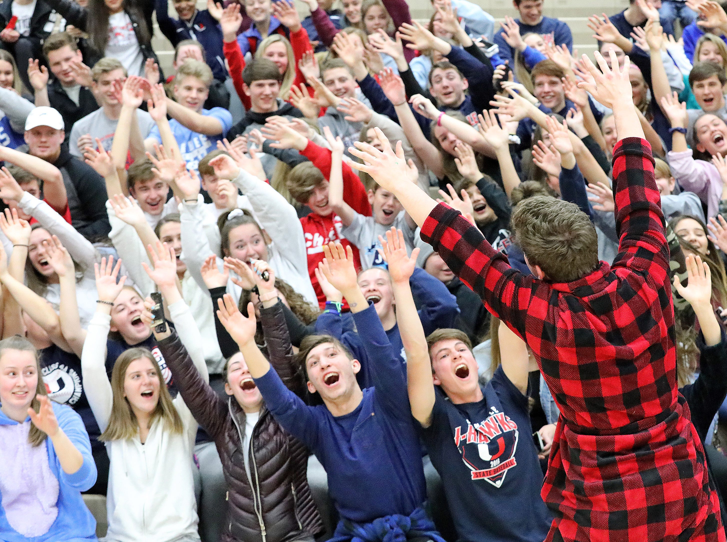 Urbandale senior Evan Smith and his red flannel bath robe fire up the students to the right as the Ankeny Hawks compete against the Urbandale J-Hawks in high school basketball on Friday, Dec. 14, 2018 at Urbandale High School. Ankeny won 62 to 52 to remain undefeated at 6-0.