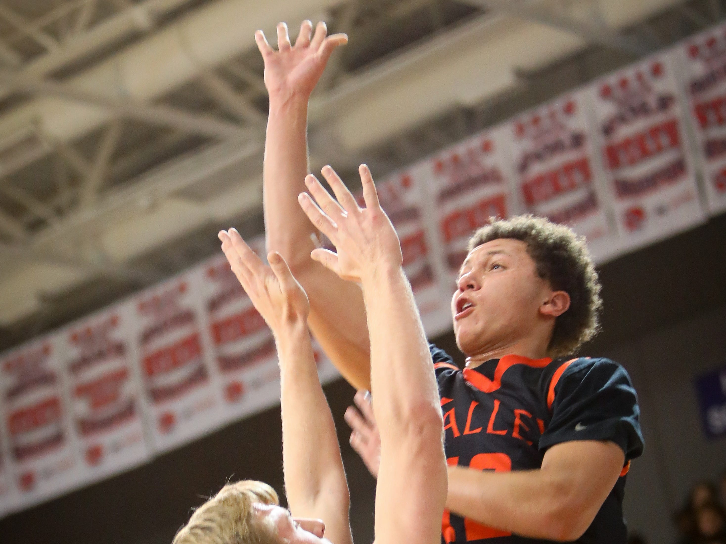 Valley senior Evan Obia floats one in over Waukee senior Trey Schaller during a boys high school basketball game between the Valley Tigers and the Waukee Warriors at Waukee High School on Dec. 14, 2018 in Waukee, Iowa.