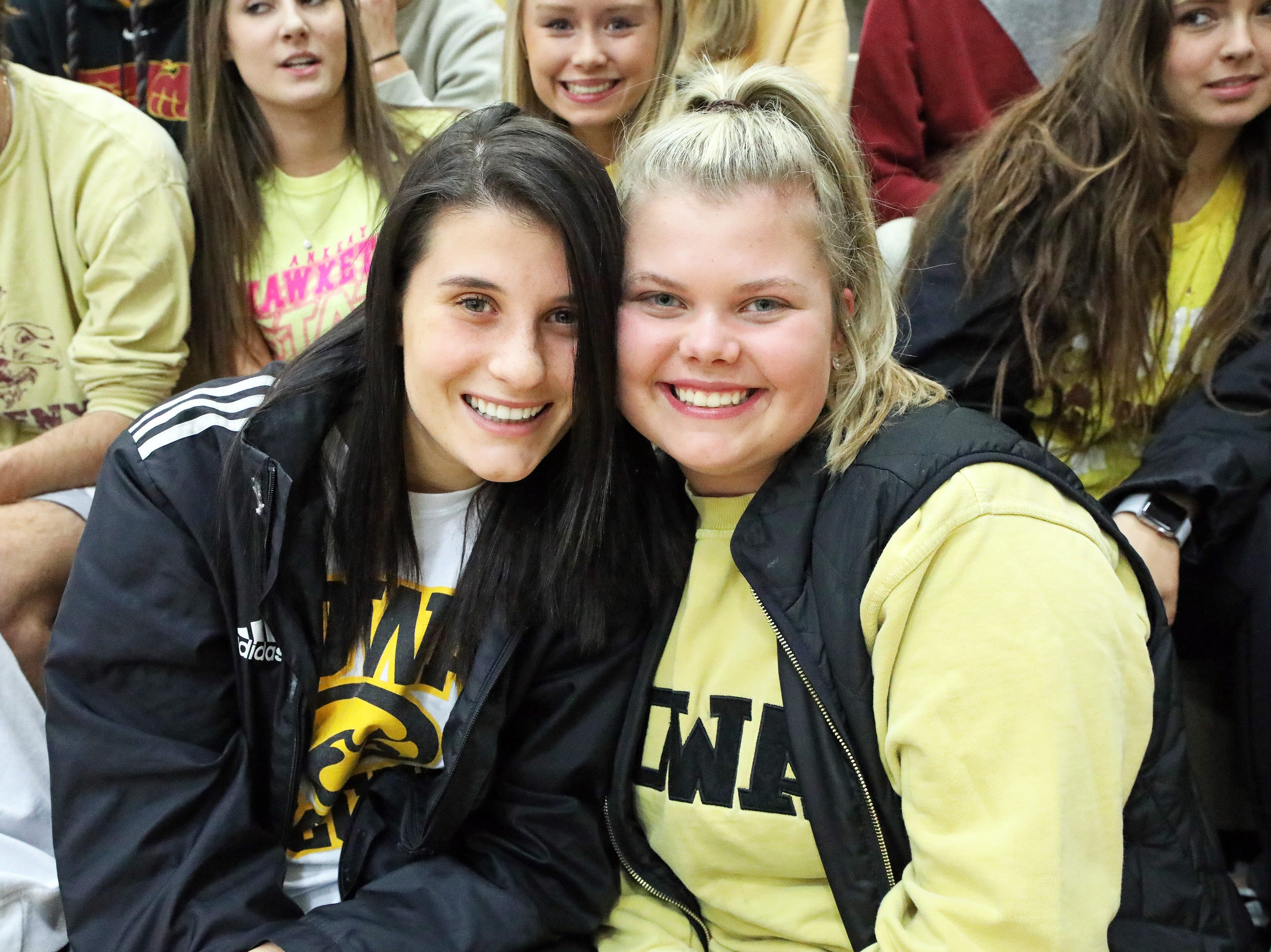 Ankeny High seniors Chloee Kooker, left, and Peyton Steinfeldt enjoy the game as the Ankeny Hawks compete against the Urbandale J-Hawks in high school basketball on Friday, Dec. 14, 2018 at Urbandale High School. Ankeny won 62 to 52 to remain undefeated at 6-0.