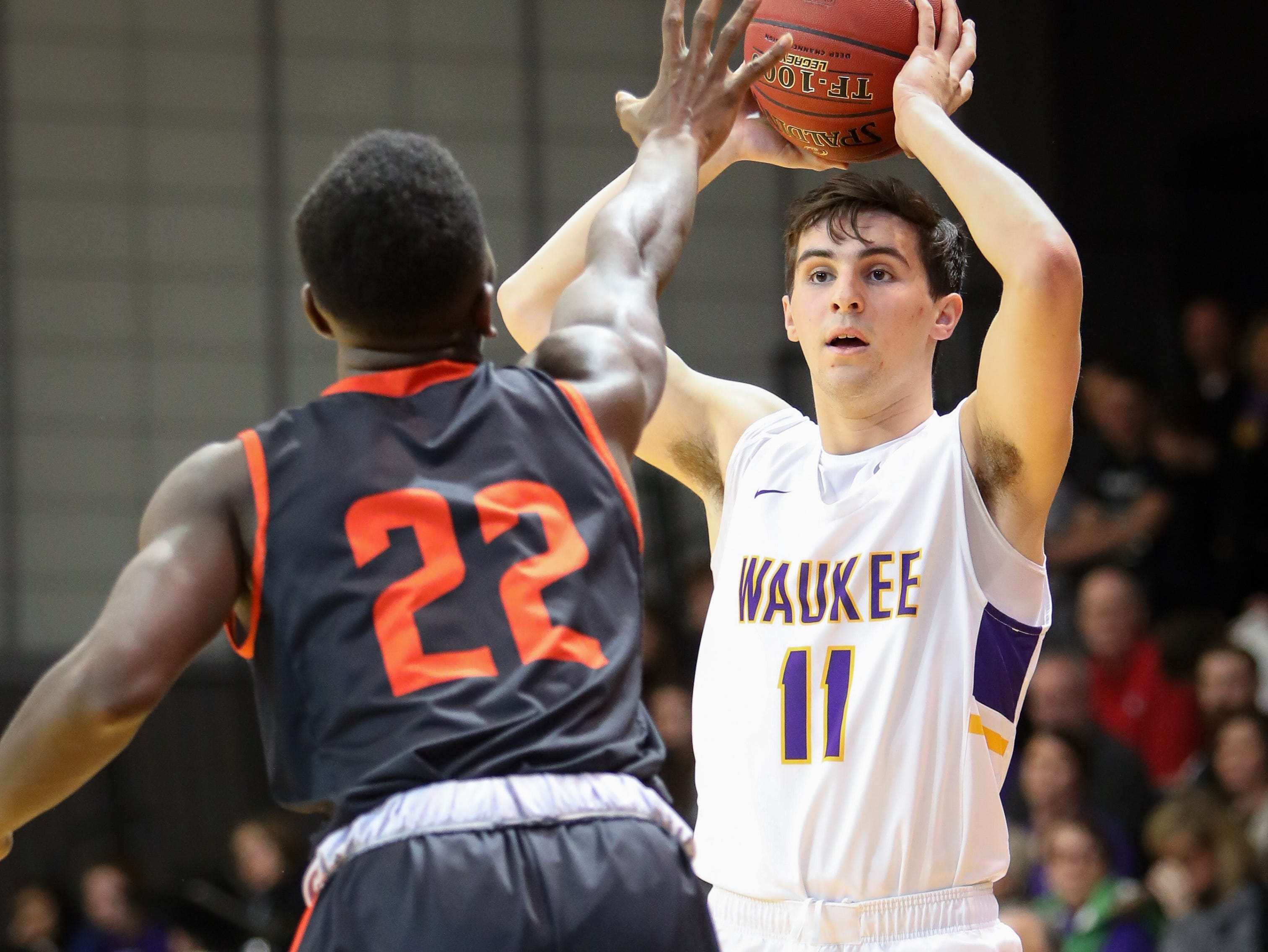 Waukee senior Noah Hart looks for an open teammate during a boys high school basketball game between the Valley Tigers and the Waukee Warriors at Waukee High School on Dec. 14, 2018 in Waukee, Iowa.
