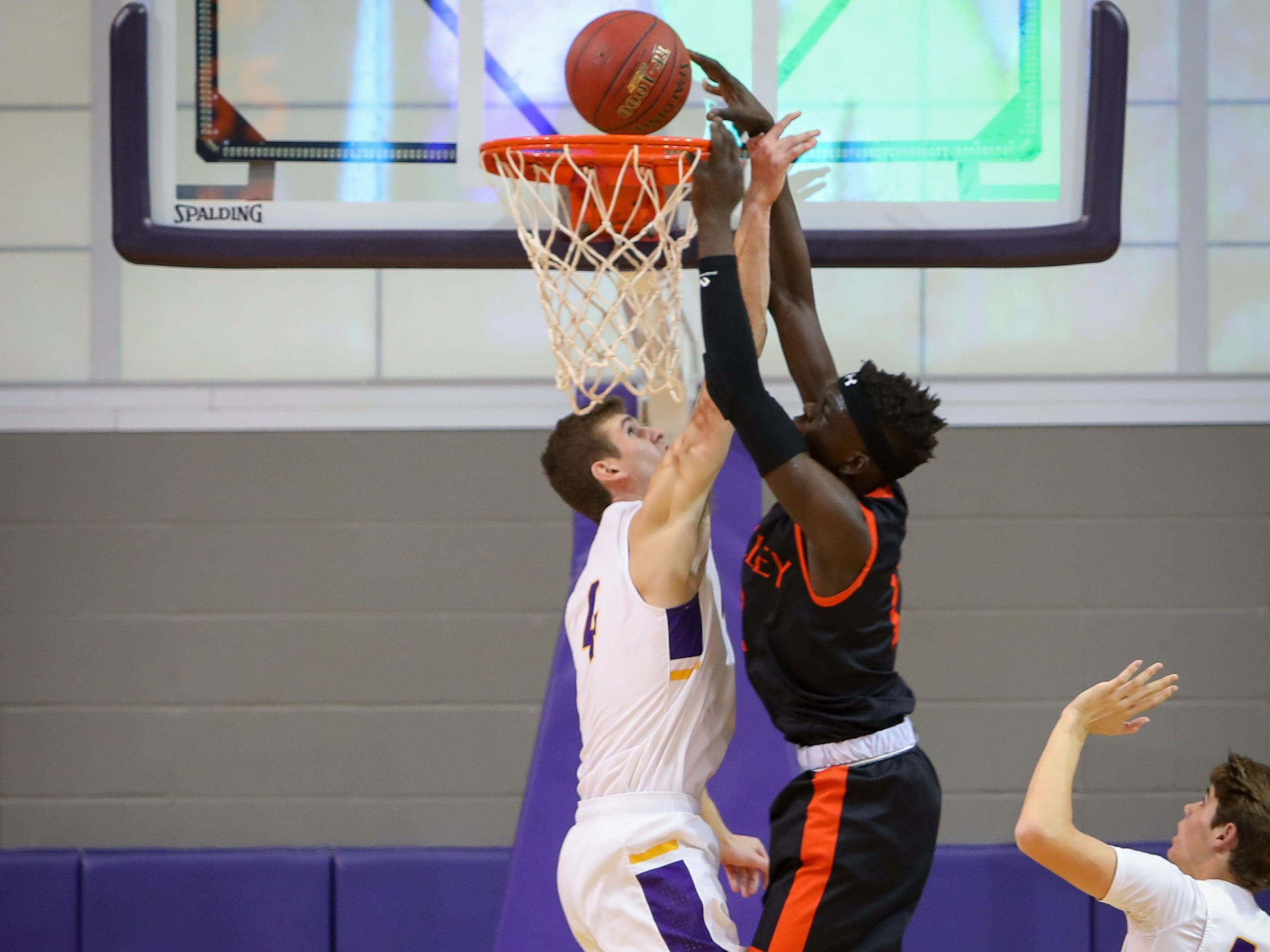 Valley senior Aguek Deng goes for a slam dunk over Waukee senior Dylan Jones during a boys high school basketball game between the Valley Tigers and the Waukee Warriors at Waukee High School on Dec. 14, 2018 in Waukee, Iowa.